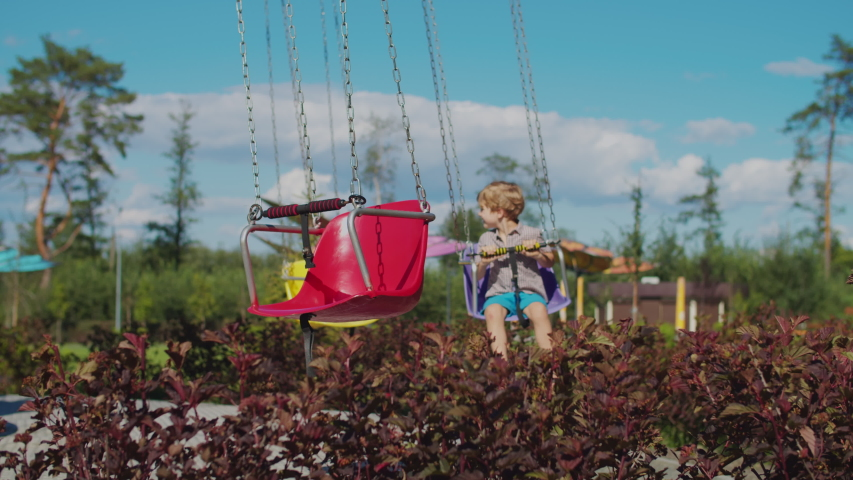 Two kids riding color chairoplane carousel in funfair. Siblings having fun alone in park. Social distance during quarantine.  Royalty-Free Stock Footage #1057310848