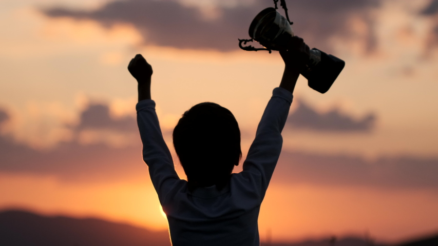 Celebrating victory winner win success concept. Silhouette of happy sport little champion sportsman, sporty little boy child holding up golden trophy cup in hand against sky raised hands. 4 K slow-mo Royalty-Free Stock Footage #1057314844