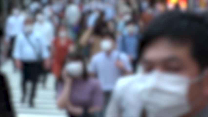 TOKYO, JAPAN - JUL 2020 : Crowd of people at the street near Shinjuku station in rush hour. Commuters wearing surgical mask to protect from Coronavirus (COVID-19) in hot summer. Blurred slow motion. | Shutterstock HD Video #1057318948