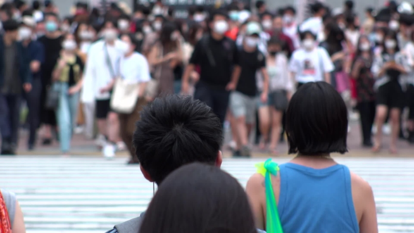 SHIBUYA, TOKYO, JAPAN - AUG 2020 : Back shot and crowd of people wearing surgical mask to protect from Coronavirus (COVID-19) at Shibuya Crossing. Shot in day time, hot summer season. Slow motion. | Shutterstock HD Video #1057319053
