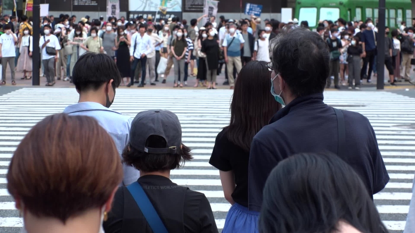 SHIBUYA, TOKYO, JAPAN - AUG 2020 : Back shot and crowd of people wearing surgical mask to protect from Coronavirus (COVID-19) at Shibuya Crossing. Shot in day time, hot summer season. Slow motion. | Shutterstock HD Video #1057319065