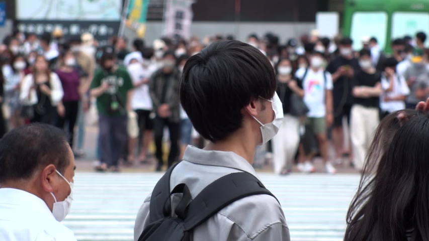 SHIBUYA, TOKYO, JAPAN - AUG 2020 : Back shot and crowd of people wearing surgical mask to protect from Coronavirus (COVID-19) at Shibuya Crossing. Shot in day time, hot summer season. Slow motion. | Shutterstock HD Video #1057319068