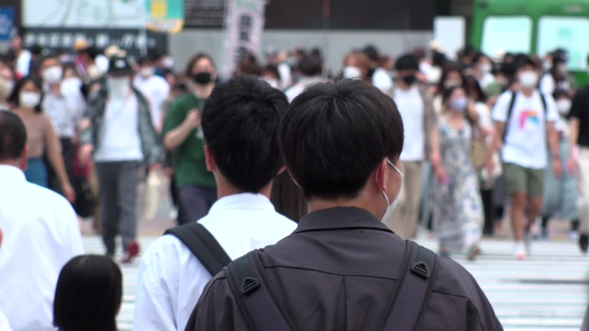 SHIBUYA, TOKYO, JAPAN - AUG 2020 : Back shot and crowd of people wearing surgical mask to protect from Coronavirus (COVID-19) at Shibuya Crossing. Shot in day time, hot summer season. Slow motion. | Shutterstock HD Video #1057319071