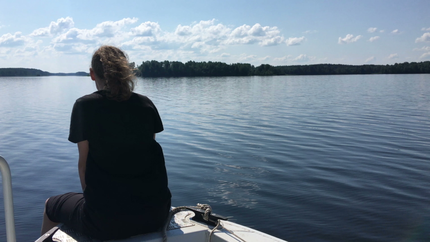 Teenager girl sits on bow of fast moving motorboat, speedboat floating on lake water surface, copyspace | Shutterstock HD Video #1057321036