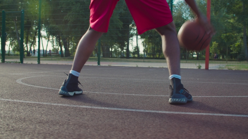 Rear view of active male basketball player practicing ball handling skill, dribbling ball between legs on outdoor court in rays of early morning rising sun during streetball training in neighborhood.   Shutterstock HD Video #1057324438
