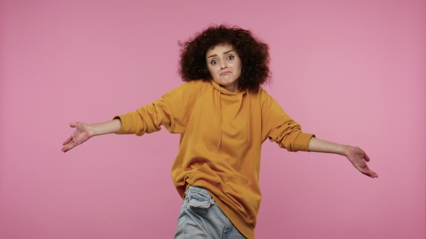 Poor student girl afro hairstyle in hoodie showing empty pockets in jeans pants, doing no money gesture, debt problems, financial crisis and bankruptcy. indoor studio shot isolated on pink background