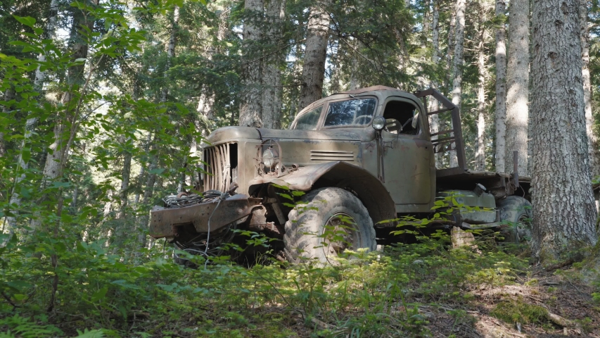 Female traveler examining abandoned vehicle in forest. Pan right view of young woman putting backpack under tree and starting to inspect derelict military truck on sunny day in forest