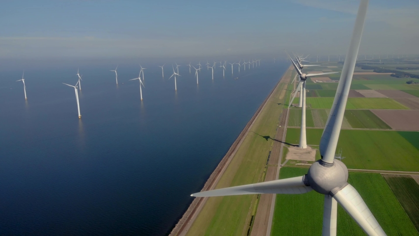 Windmill park green energy from drone view, windmill ofsshore wind farm in the Netherlands windmill turbines. High quality 4k footage Royalty-Free Stock Footage #1057331323