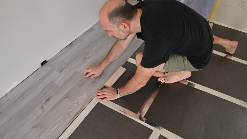 The Caucasian handyman places the new gray laminated wood plank on the edge of the one already on the floor. With the wooden block and the hammer fixed it, check with your finger the perfect closure. | Shutterstock HD Video #1057332547