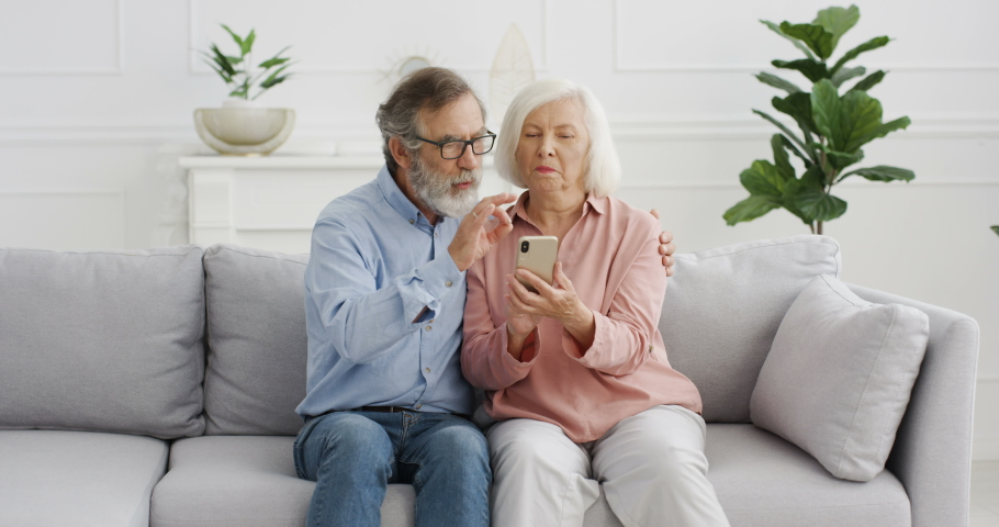 Old Caucasian cheerful couple sitting on couch and watching something on smartphone screen and talking. At home. Senior retired man and woman using mobile phone, tapping and scrolling, discussing.