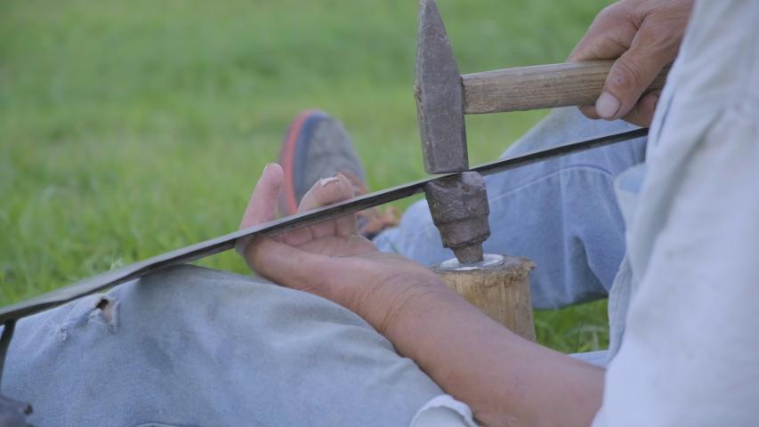 4k video of senior man peening scythe blade with hammer. | Shutterstock HD Video #1057332799