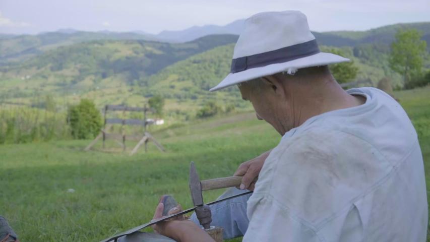 4k video of senior man peening scythe blade with hammer. | Shutterstock HD Video #1057332802