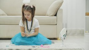 Cute little girl sitting on the carpet, looking in the mirror, wearing a bracelet, necklace, headgear and different hair clips, posing.