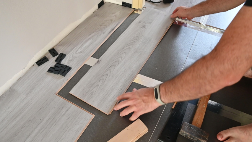 Close up shot on the laying of a new gray laminated wood plank on the edge of the one already on the floor. With the wooden block and the hammer fixed, the finger checks the perfect closure. | Shutterstock HD Video #1057334755