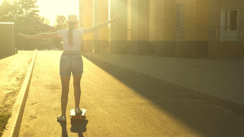 Free teen Girl learns to ride a skateboard on the street in the sun. happy skateboarder rides on road in the city at sunset.   Shutterstock HD Video #1057334917