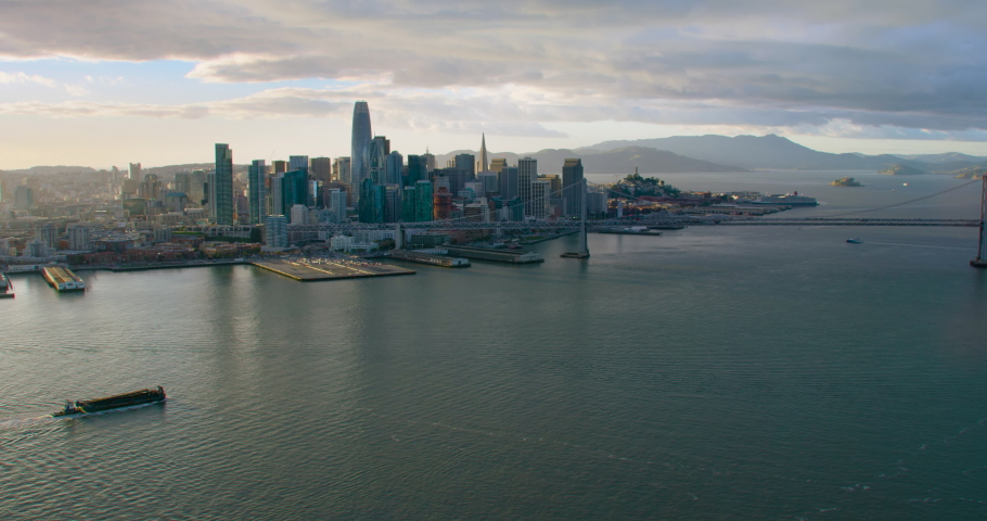 Aerial view of San Francisco skyline. Famous skyscrapers over a blue sky. Oakland Bay Bridge. California, United States. Shot on Red weapon 8K.
