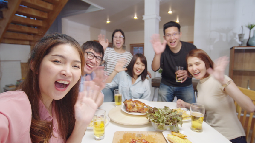 Group of young Asian people at home dinner party, looking at camera, greeting friends on remote video call. Point of view vlog or selfie camera. New normal lifestyle, social distancing concept Royalty-Free Stock Footage #1057347607