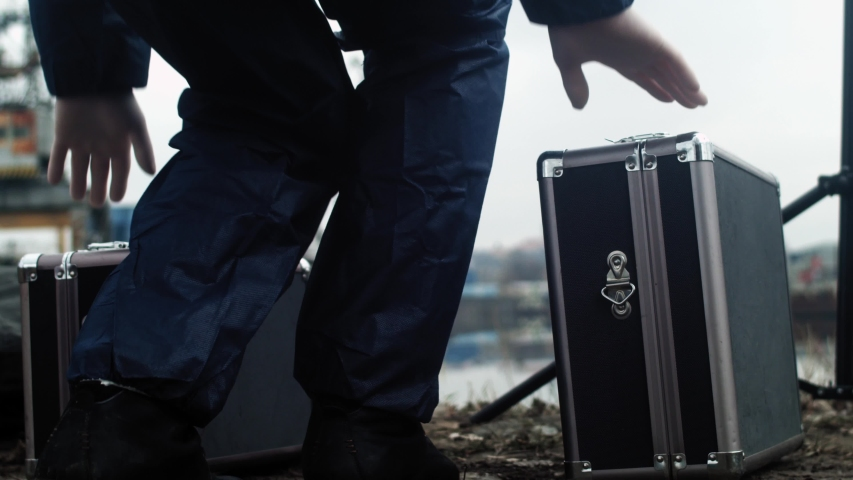 Detective with suitcases walking towards murdered person, crime scene investigation