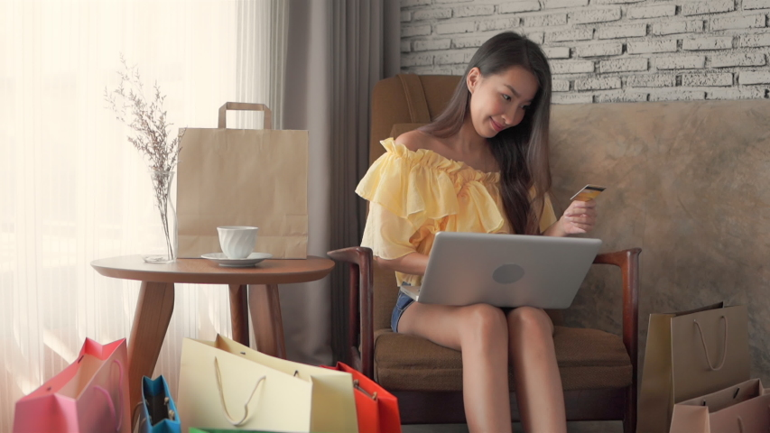 Young asian woman using her credit card to pay for her online shopping while in the comfort of her own house. Royalty-Free Stock Footage #1057349194