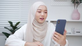 Beautiful Asian Muslim Woman in hijab making a video call smiling and talking with her friend and family. Businesswoman having video call discussing, working online meeting with team at home office
