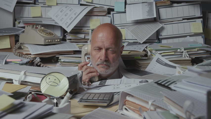 Sad frustrated business executive overwhelmed by work, he is overloaded with paperwork and answering phone calls in the office | Shutterstock HD Video #1057352173