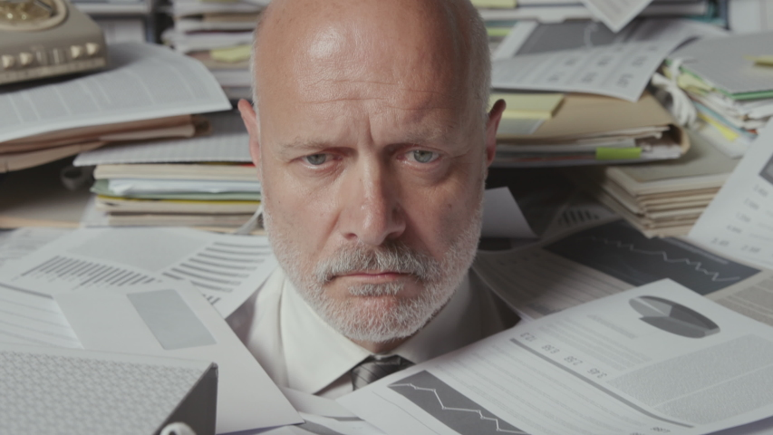 Sad stressed businessman working in his office, he is sitting under a lot of paperwork and he is overwhelmed by work