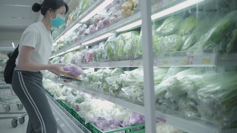 4k Young Asian woman Getting food at grocery store looking at vegetables shelf, supermarket chain, stock up food supply, during covid19 lockdown  corona virus pandemic, female wearing medical mask