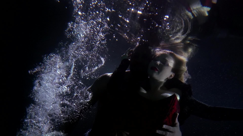 Close-up of a man and a girl, they are at the depth of water on a dark background, around them float bubbles and the fabric of a bright skirt, they are beautifully hugging and warming themselves | Shutterstock HD Video #1057353895