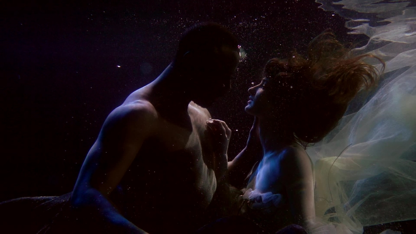 Close-up portrait of a African-American man and girl, they are at the depth of water on a dark background, around them float bubbles and fabrics, they are beautifully embracing, they have passion. | Shutterstock HD Video #1057353901