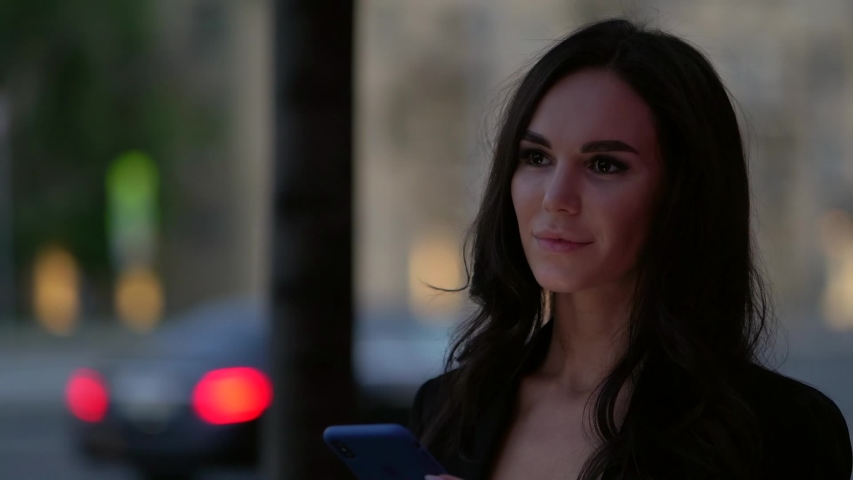 Close-up portrait of a bright dark-haired girl against the background of the evening lights of the city, walking near the highway | Shutterstock HD Video #1057353910