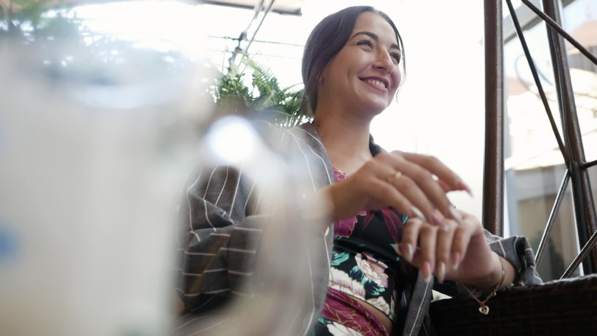 Young pretty cheerful woman smiling and laughing in cafe or restaurant outdoors. | Shutterstock HD Video #1057354093