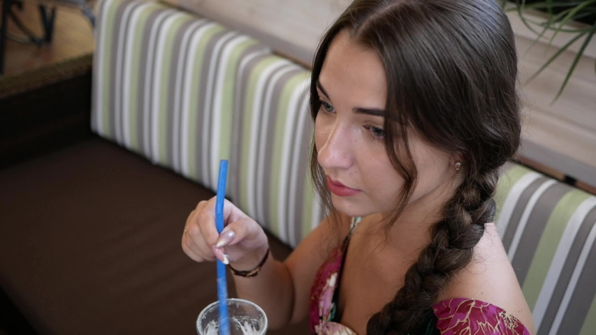 Beautiful young woman in restaurant stir cocktail straw in anticipation. | Shutterstock HD Video #1057354426