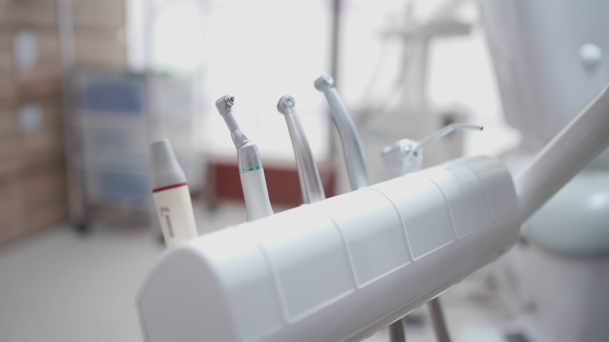 Process of hygienic preparation of dental clinic tools. Staff wearing white PPE suit wrapping dental operation equipment, preparing before dentistry operating professional, sterile contaminated items | Shutterstock HD Video #1057354543