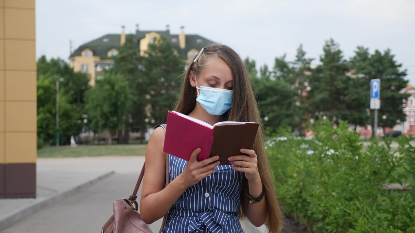 Girl student in medical mask walk near with a book. pandemic coronavirus education concept covid 19. girl student walk in medical mask. studying near the university during go coronavirus a period | Shutterstock HD Video #1057354660