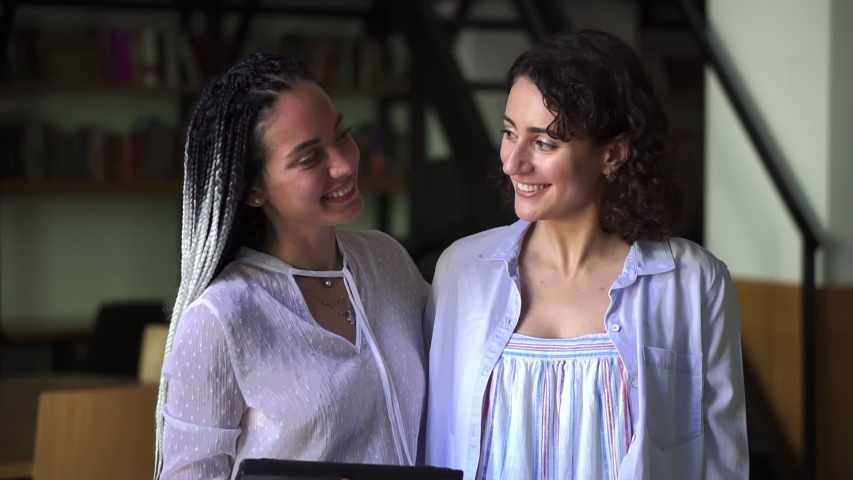 Portrait of two pretty young caucasian women in white blouses standing in library and smiling in camera, academic friends | Shutterstock HD Video #1057354846