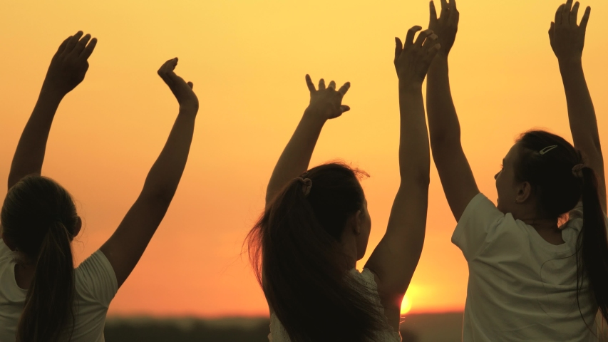 Free girls are dancing cheerfully on summer evening at sunset. healthy teenagers having fun raise their hands up. celebration in the open air. Celebrate a summer day at a beach party | Shutterstock HD Video #1057354957