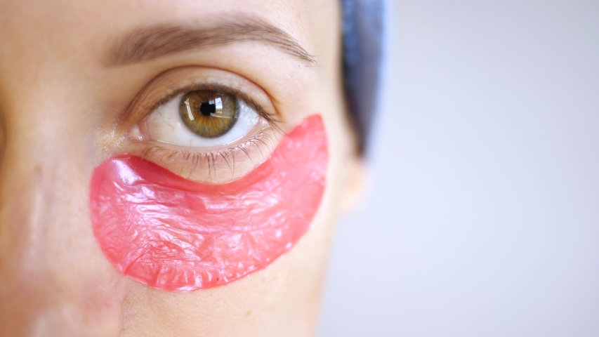 Young woman after bath or shower with towel on your head used pink collagen hydrogel cosmetic patches under eyes. Lifting of wrinkles. Skin care at home. Cosmetology procedure. | Shutterstock HD Video #1057355194