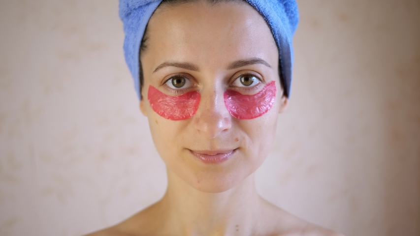 Beautiful young woman applying collagen eye masks on face. Portrait of happy girl smiling and posing in studio for advertising. | Shutterstock HD Video #1057355224