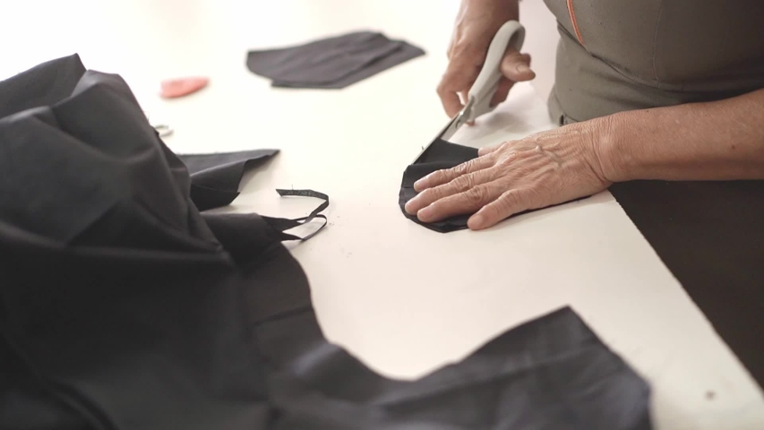 Clothing designer. Woman hands working on fabric. Seamstress at the job. Face mask pre production. | Shutterstock HD Video #1057355236