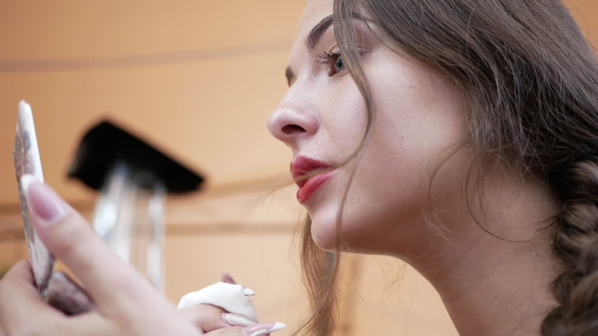 Young beautiful woman preening in a cafe, adjusting her lipstick close-up. | Shutterstock HD Video #1057355272