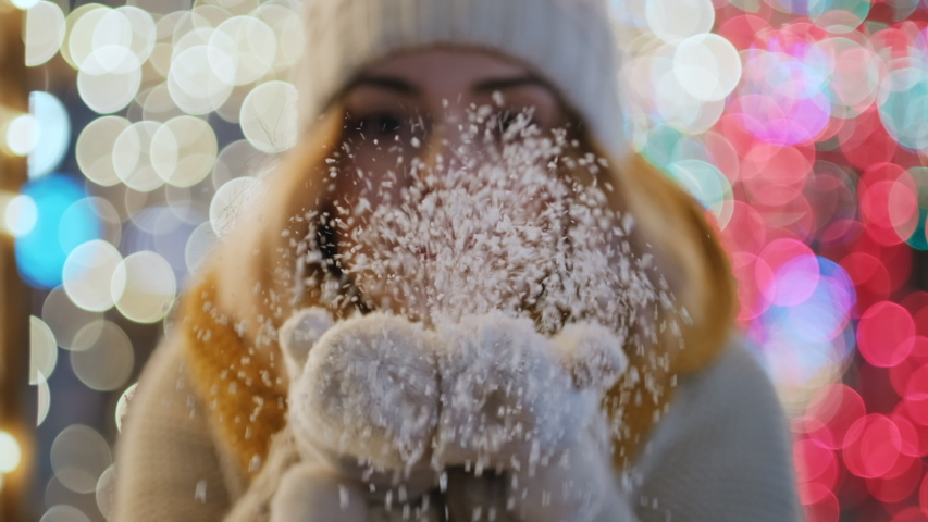 Portrait young woman blowing snow from hands in warm mittens and caps looking at camera smiling bokeh Christmas lights in city square slow motion. Flying snowflakes. Christmas symbol. Noel. Emotions | Shutterstock HD Video #1057355641