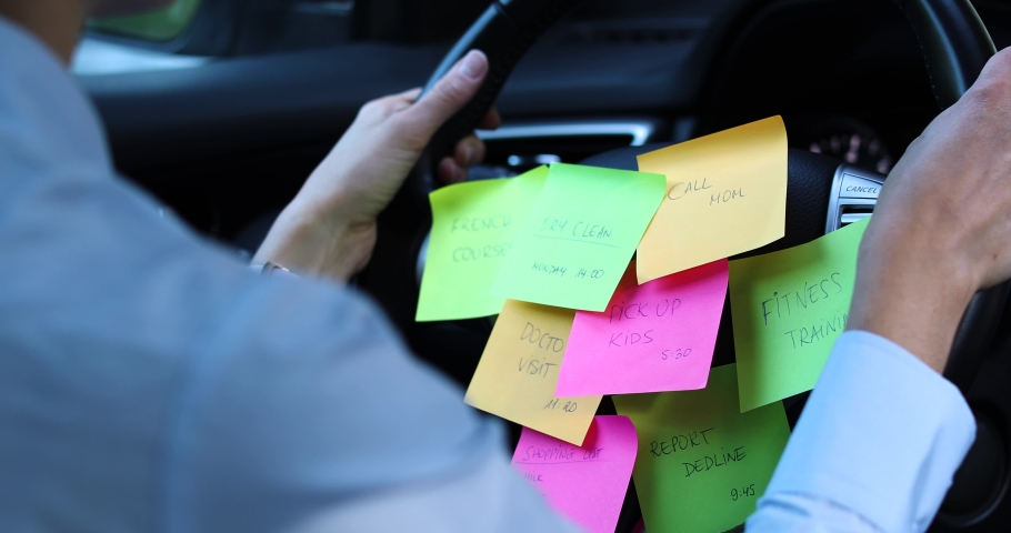 Busy day schedule concept - woman driving car with to do list notes on the wheel | Shutterstock HD Video #1057355650