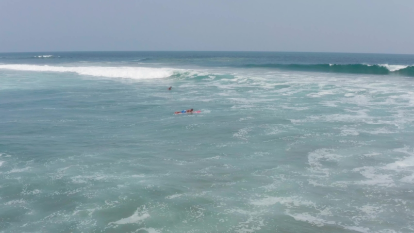 Surfers on Boards in Water of Pacific Ocean Waiting For Good Wave, Acapulco, Mexico, Aerial View