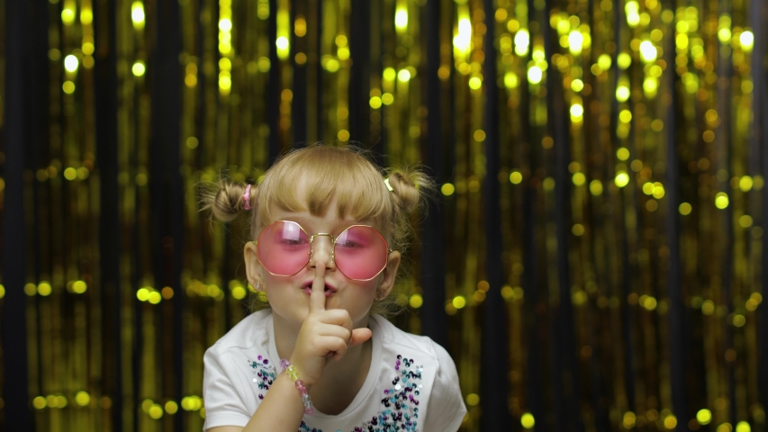 Child putting finger on lips making silence gesture, asking to keep secret. Shh. Be quite. Little fun blonde kid teen teenager girl 4-5 years old in sunglasses on background with foil fringe curtain | Shutterstock HD Video #1057357762