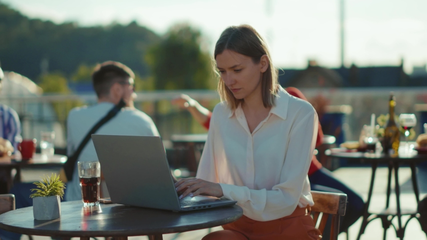 Serious beautiful young woman sitting at table with laptop in cafe working online typing internet online communication technology business outdoors slow motion