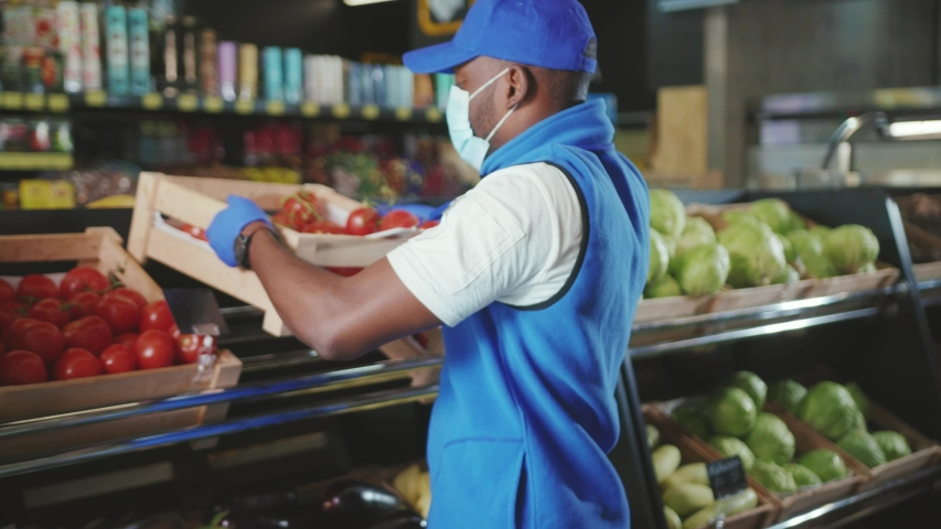 Shot of african american sales wear gloves and mask consultant working in supermarket market store black food seller shop grocery holding job organic market staff slow motion