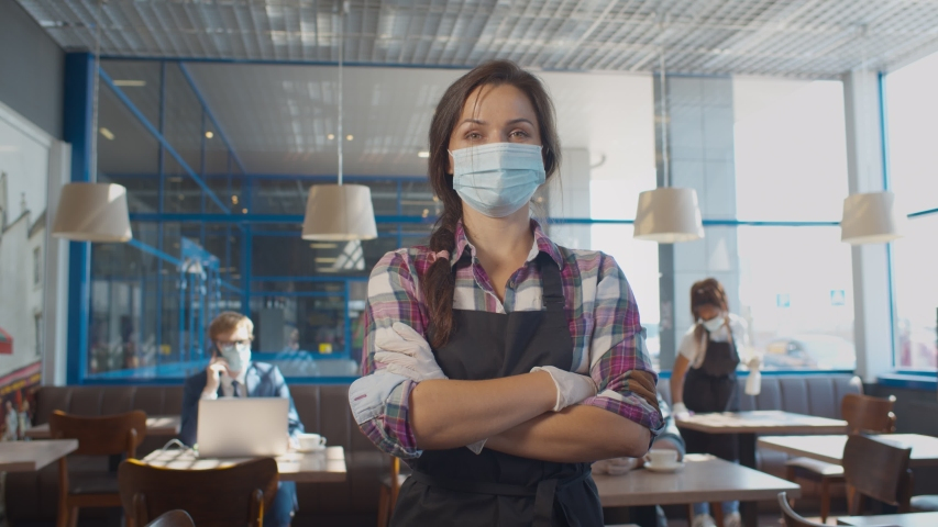 Portrait of waitress wearing face mask and gloves while serving in coffee shop. Pretty restaurant worker in apron and protective mask and gloves posing at camera with crossed hands | Shutterstock HD Video #1057360411
