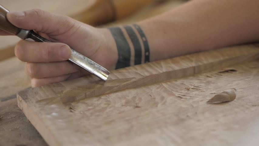 A woodcarver processes a wooden board with a chisel and mallet. craftman making a tea tray | Shutterstock HD Video #1057366471