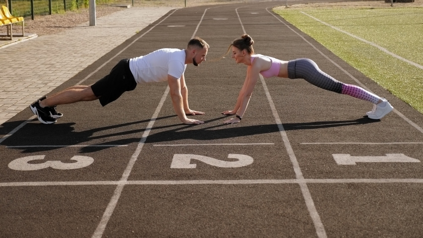Sports active man and woman train in the summer outdoors in a public stadium, they stand in the plank and slap each other's hands. | Shutterstock HD Video #1057373956