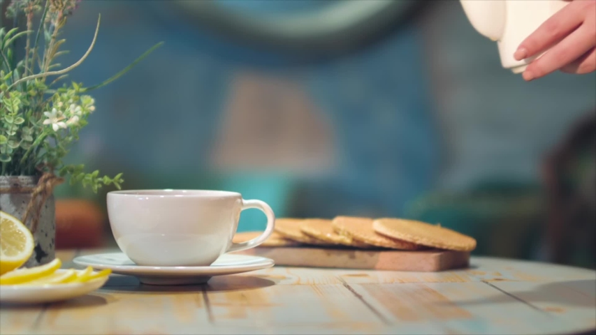 Woman's hand pouring tea from glass jug into a cup of tea. Breakfast concept. Lemon slices. Tea time. Royalty-Free Stock Footage #1057374232